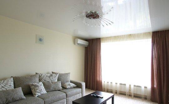 Белый глянцевый натяжной потолок в гостиной