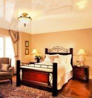 Белый глянцевый натяжной потолок в спальне