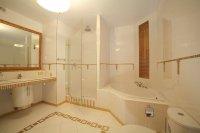 Белый натяжной потолок в ванной с люстрой