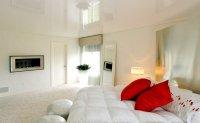 Одноуровневый глянцевый натяжной потолок в спальне