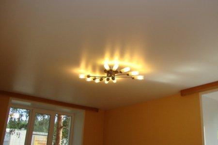 Сатиновый натяжной потолок в гостиной с люстрой