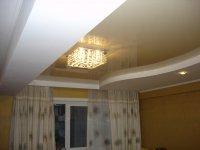 Спальня с бежевым потолком и люстрой